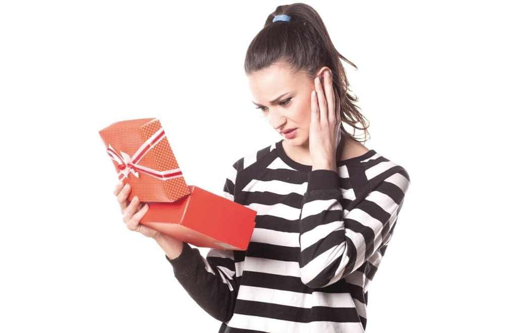 WHAT TO DO WITH UNWANTED GIFTS, HOW TO DEAL WITH UNWANTED GIFTS, WOMAN RECEIVING A GIFT SHE DOESN'T LIKE