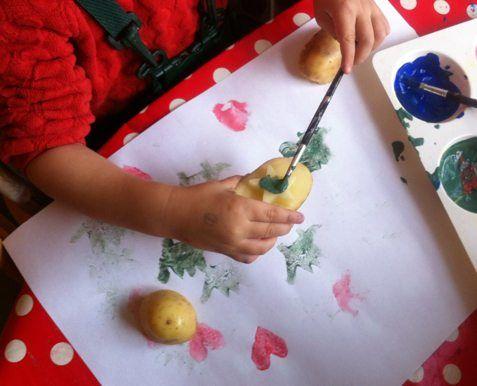 Toddler painting potato stamp
