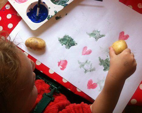 Toddler using potato stamps to make art
