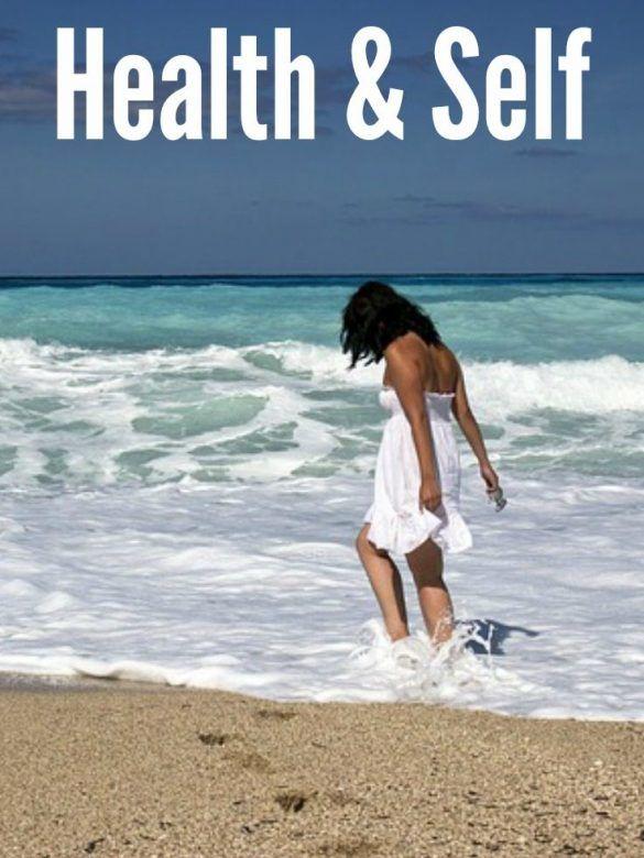 Health & Self, woman walking along beach paddling in sea